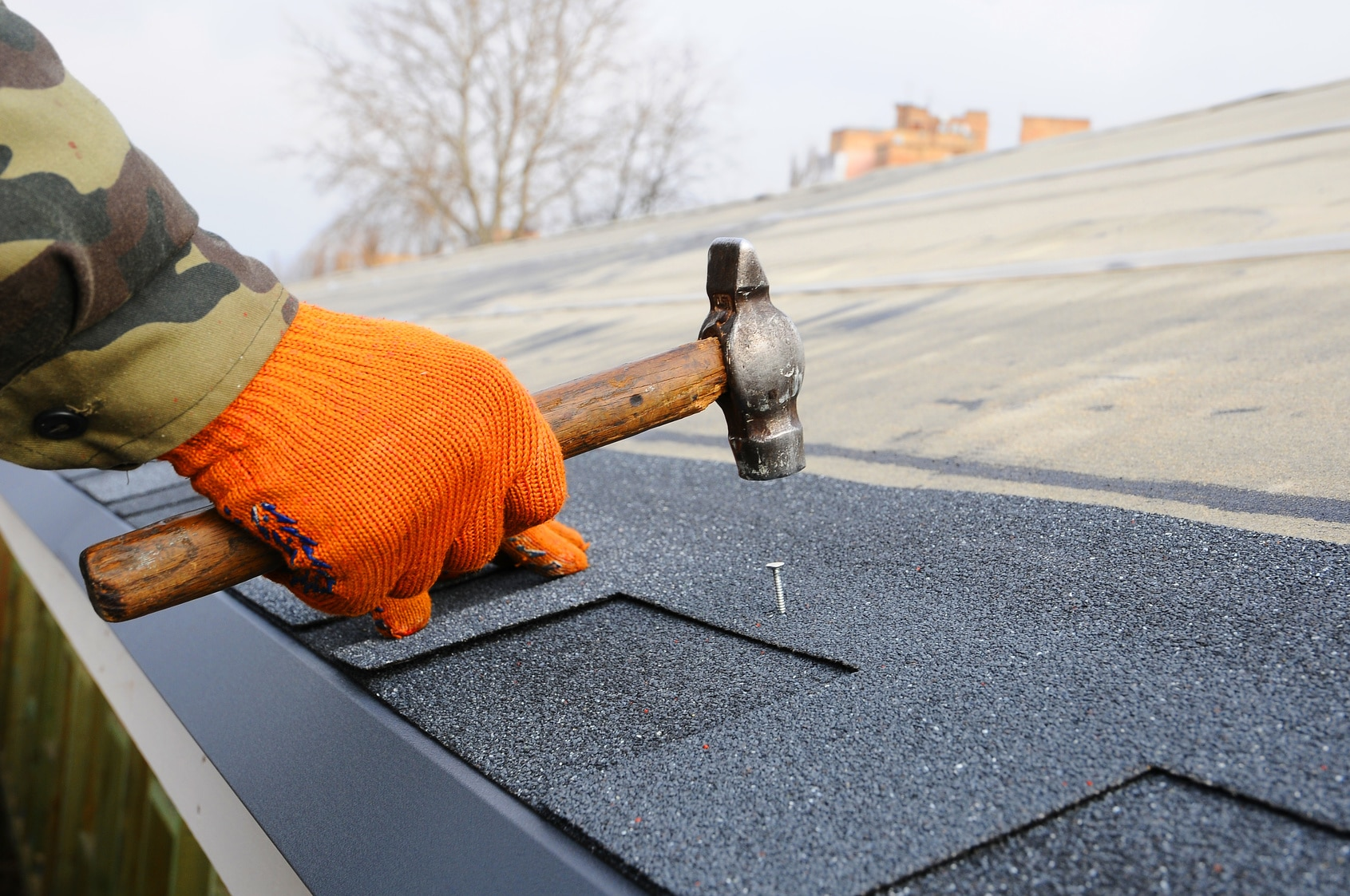 Waterproof your roof to prevent water damage - ServiceMaster Disaster Associates, Inc. in Stoneham, MA - someone hammering down a shingle on the roof